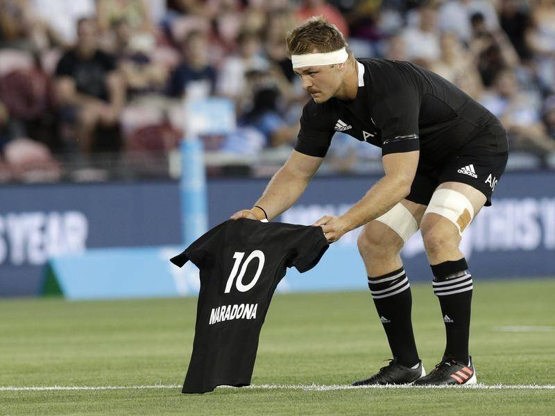 Sam Cane laying an All Black number 10 jersey on the Newcastle pitch in memory of Diego Maradona.